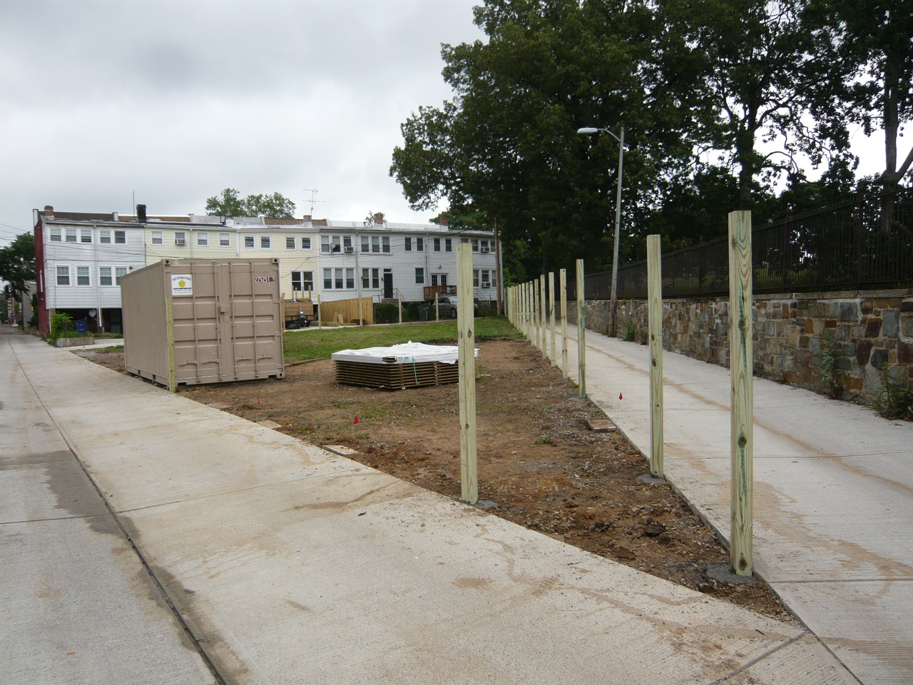 Fence posts on the lot with view of future garden bed area in foreground
