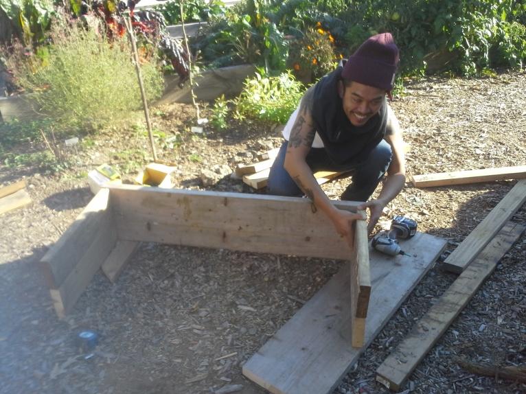 A friend making a compost bin out of my scrap lumber
